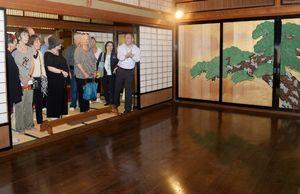 ガイドの案内で、旧高取邸の能舞台を見学する外国人客=唐津市北城内