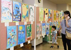 子どもたちが家族を描いた、思い思いの作品180点が並ぶ=佐賀市のミサワホーム佐賀