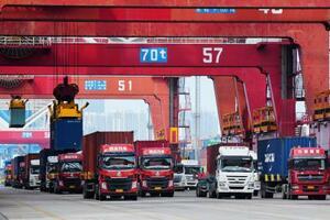 6月、中国山東省の青島港に並ぶ、コンテナ輸送のトラック(AP=共同)