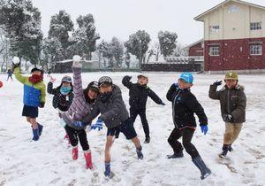 運動場に積もった雪に歓声を上げ、雪合戦を楽しむ子どもたち=武雄市の武雄小(11日午前10時ごろ)