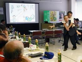 デモンストレーションを交えた講演などで防犯や災害時の活動について学んだ研修会=佐賀市のメートプラザ佐賀