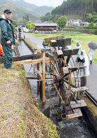 雨の中、用水路に設置され、回り出した水車=唐津市相知町町切