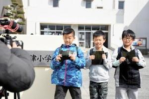 強風によるハプニングにめげず、佐賀のりをPRするCM撮影に臨む児童たち=小城市の牛津小学校