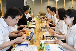 全6種類ある「2019さが総文おもてなし弁当」を試食する白水敏光教育長(左)や生徒ら=佐賀市の県庁