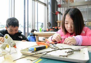 「古代の森体験館」に愛称が変わったことを記念して始まった木工クラフト体験に挑戦する参加者=神埼市郡の吉野ケ里歴史公園