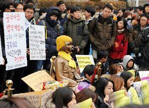 安倍政権と韓国の朴槿恵政権による従軍慰安婦問題での政府間合意に抗議し、ソウルの日本大使館前で開かれた集会。中央は慰安婦被害を象徴する少女像=2015年12月30日(共同)