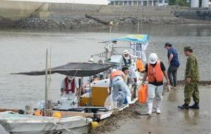オスプレイの騒音がコノシロ漁に与える影響の調査を終え、船から機材を運び出す委託業者ら=藤津郡太良町の竹崎漁港