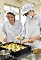 管理栄養士の副島たづ子さん(左)の指導を受けながら具材を盛り付ける学生=佐賀市の佐賀女子短期大学