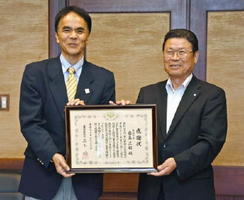 福岡国税局の並木稔局長(左)から感謝状を受け取り笑顔を見せる岩島正昭町長=太良町役場