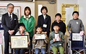 上田卓史幹事(左上)から表彰状を受け取った生徒たち=佐賀市の嘉瀬小学校