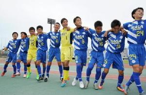サッカー男子で優勝し、肩を組んで喜ぶ佐賀東の選手たち=佐賀市の県総合運動場陸上競技場