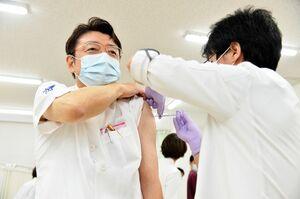 新型コロナウイルス感染症のワクチン接種を受ける佐賀大医学部附属病院の山下秀一院長=15日午前、佐賀市の同病院