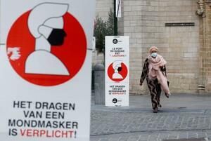 ブリュッセル中心部でマスクの着用義務を呼び掛ける看板=16日(ロイター=共同)