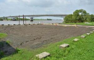 大雨で打ち上げられた泥が堆積し、立ち入り禁止となっている駐車場。奥には桟橋があり、エツ漁の船が停泊している=久留米市城島町の下田大橋そば