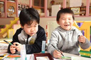絵馬に笑顔で願い事を書き込む子どもたち=吉野ヶ里町の三田川児童館