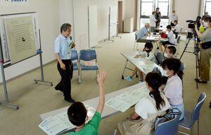 講師の藤永勝之さん(左)から囲碁を教わる子どもたち=鹿島市生涯学習センターエイブル