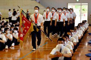 大きな拍手の中、優勝旗を先頭に体育館に入場する選手たち=基山町の東明館