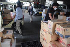 洗剤やおむつなどの物資を譲渡先の車に積み込む職員ら=佐賀市役所久保田支所