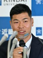 阪神から1位指名され、笑顔で記者会見する近大の佐藤輝明内野手=26日、大阪府東大阪市