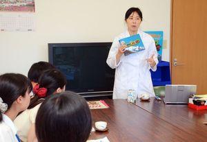 参加した学生たちに既存の商品パッケージを紹介する竹下製菓の竹下真由社長=小城市の竹下製菓