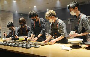 料理を盛り付ける目黒浩太郎シェフ(中央)ら=有田町赤坂のアリタハウス