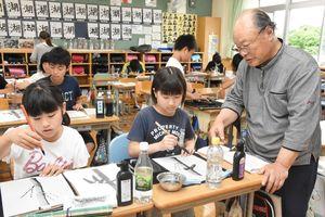 吉村正幸さん(右)から墨絵を学ぶ相知小の6年生=唐津市相知町の同小