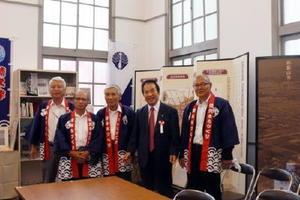 楠久・津歴史ふれあい館のオープンに尽力したまちづくり実行委員会のメンバーと塚部芳和市長(右から2人目)。日本の近代化に貢献した郷土の歴史を誇るパネル展示などが用意されている=伊万里市山代町