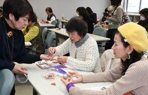 青栁伊都子さん(左)に教わりながら、ひな人形を折る参加者=佐賀市のアバンセ