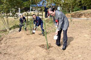 「古代人の森」の整備に向けて植樹する深浦弘信伊万里市長(右)ら=伊万里市山代町楠久