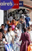 GW初日から大勢の買い物客が詰め掛けた鳥栖プレミアム・アウトレット。大きな買い物袋を両手に提げる姿も=4月27日、鳥栖市