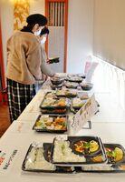 日本料理店「旬彩響宴おかぎ」は、「#TEAMサガハピ」に加盟し、近隣の飲食店のテイクアウト商品を取り扱っています。5~8店舗がハンバーグやから揚げなどがメーンの弁当をそろえ、価格は500円~1000円です。飲食に関係する人々を応援しようと、屋外ブースでは野菜や加工食品などの直売所も設置しています=佐賀市兵庫北の同店