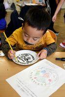 筆で絵付けに挑戦する子どもたち=唐津市の伊岐佐小