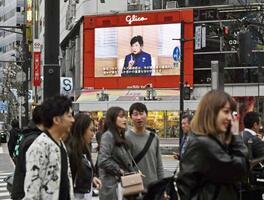 東京・渋谷のスクランブル交差点前の大型モニターに流れる、新型コロナウイルスの感染拡大防止を呼び掛ける小池百合子都知事の映像=28日午後