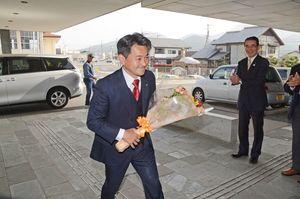 職員から贈られた花束を手に初登庁する松尾佳昭有田町長=町役場