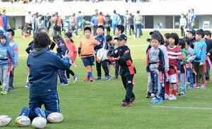 ラグビーボールでパスを練習する子どもたち