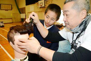理容師の指導を受けながらマネキンの髪をバリカンで刈る児童=唐津市の平原小
