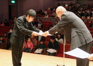 緑光会の田代利夫代表(右)から最高賞を表彰を受け取る山内亮人さん=佐賀市の県立美術館ホール