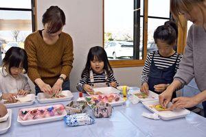 モザイクチップコースター作りに挑戦する家族連れ=基山町図書館