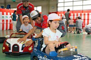 電動カーに乗って学生と楽しむ園児たち=佐賀市の佐賀工業専門学校