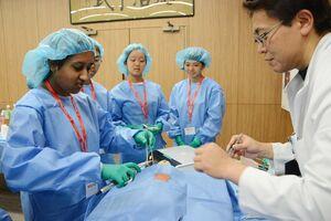 止血しながら切開できる「超音波凝固切開装置」の操作を体験する中高生ら=佐賀市の県医療センター好生館