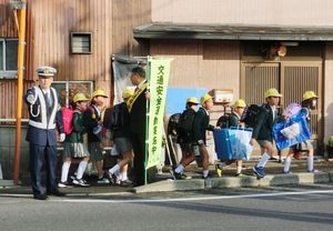 並んで歩道を歩き、学校へ向かう児童と安全運転を呼び掛ける神埼署員ら=神埼中学校前交差点(提供写真)