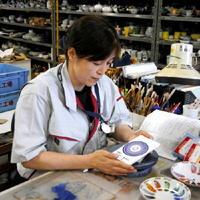 チーフとして絵の具の発色具合を確認する立石郁子さん。「今、職場で筆を持つのはこの時くらい」と話す=有田町の香蘭社赤坂美術品工場