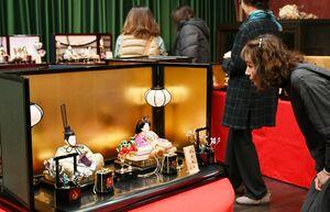 色鮮やかな佐賀錦をまとったひな人形を眺める来場者=佐賀市の岡田三郎助アトリエ