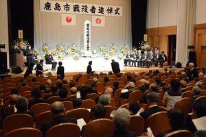 追悼式で献花する参列者=鹿島市生涯学習センター
