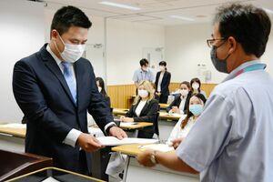 奨学金の決定通知書を受け取る留学生=佐賀市の佐賀商工ビル