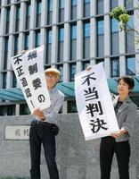 九州電力川内原発1、2号機設置許可の取り消しを求めた訴訟で請求が認められず、福岡地裁前で「不当判決」の垂れ幕を掲げる原告側=17日午前