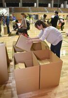 札幌市が実施した防災訓練で、段ボールベッドの組み立てを体験する市民ら=14日午前
