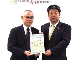 ちらしを手にする中谷正一佐賀支店長(左)と力久芳則取締役=佐賀市の日本政策金融公庫佐賀支店