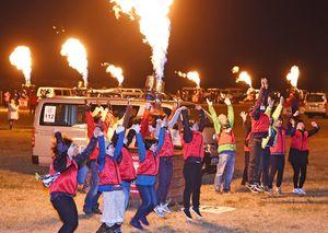 音楽に合わせて一斉にバーナーの炎を上げ、盛り上がるバルーンクルー=佐賀市の嘉瀬川河川敷