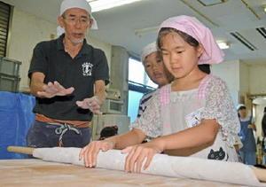 アドバイスを受けながら、麺棒でそばをのばす児童=上峰町のふるさと学館